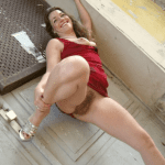 Roxanne squatting, peeing and smiling, holding the hem of her…